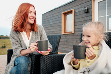 A Young Mother And Little Daughter Sit In Chairs In Warm Rugs And Drink Tea From The Mugs On The Terrace Of A Wooden House. Autumn Evening In The Country.
