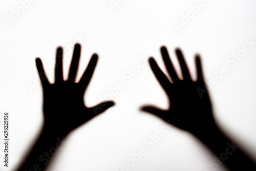 Fotomural  Dark silhouette of female hands on white background, concept of fear