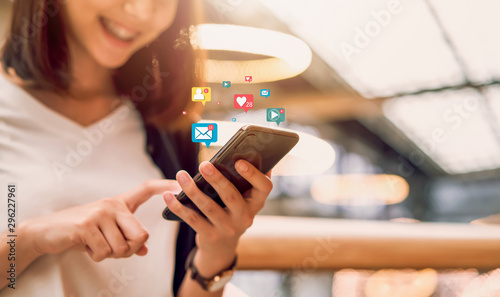 Foto  Social media and digital online concept, smiling Asian woman using smartphone and show technology icon