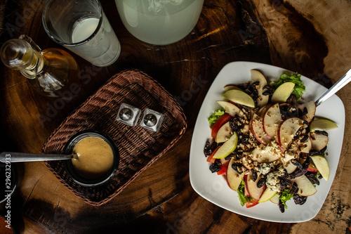 saludable ensalada de manzana, nuez, queso azul y aderezo, ubicada en la mesa de madera con refresco natural Canvas Print