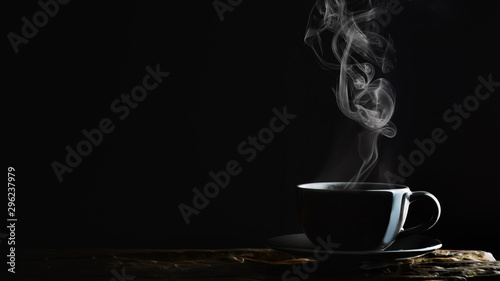 Spoed Fotobehang Thee beverage background of hot coffee, tea or chocolate in black cup on wooden plank in dark background