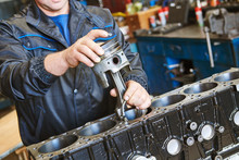 Diesel Truck Engine Repair Service. Automobile Mechanic Installing Piston Into Engine