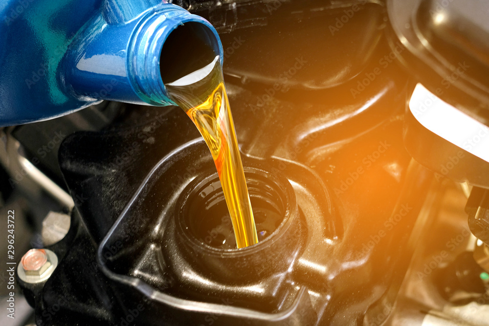Fototapeta Refueling and pouring oil quality into the engine motor car Transmission and Maintenance Gear .Energy fuel concept.
