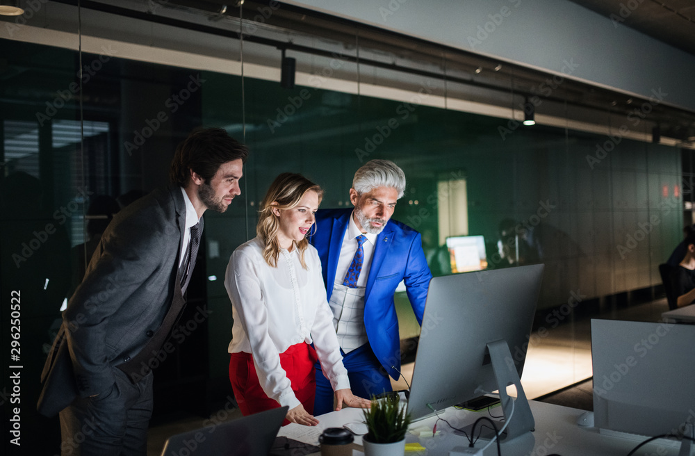 Fototapety, obrazy: A group of businesspeople in an office at night, using computer.