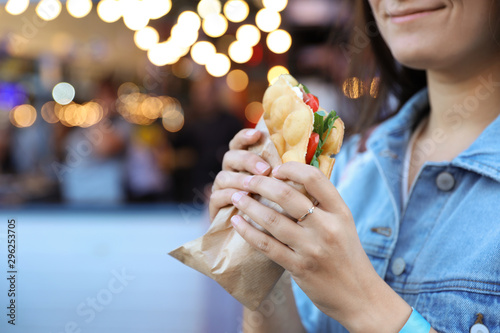 Fotografía  Young woman holding delicious bubble waffle with tomato and arugula outdoors, cl