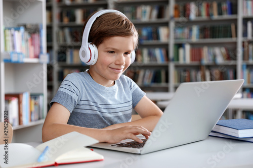 Little boy with headphones reading book using laptop in library Fototapet