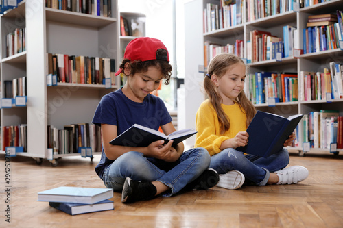 Cute little children reading books on floor in library