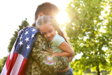 Father In Military Uniform With American Flag Holding His Little Daughter At Green Park