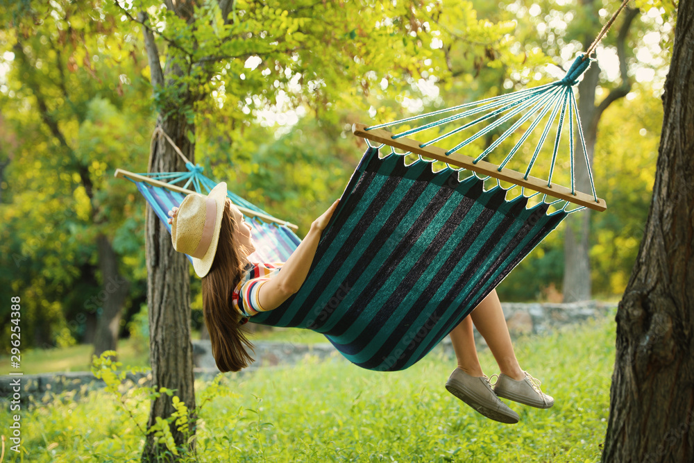 Fototapeta Young woman resting in comfortable hammock at green garden
