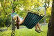 canvas print picture - Young woman resting in comfortable hammock at green garden