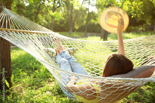 Fototapeta Young woman with hat resting in comfortable hammock at green garden obraz