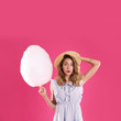 Leinwandbild Motiv Emotional young woman with cotton candy on pink background