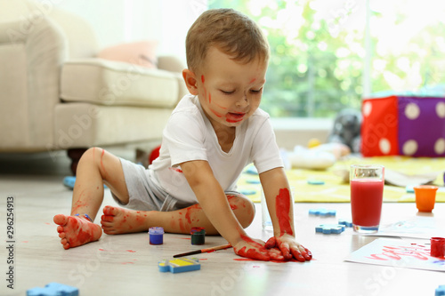 Fotografia Cute little boy playing with paints on floor in living room