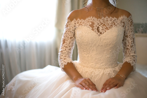 Figure of girl in the wedding dress sits alone in the room near the window