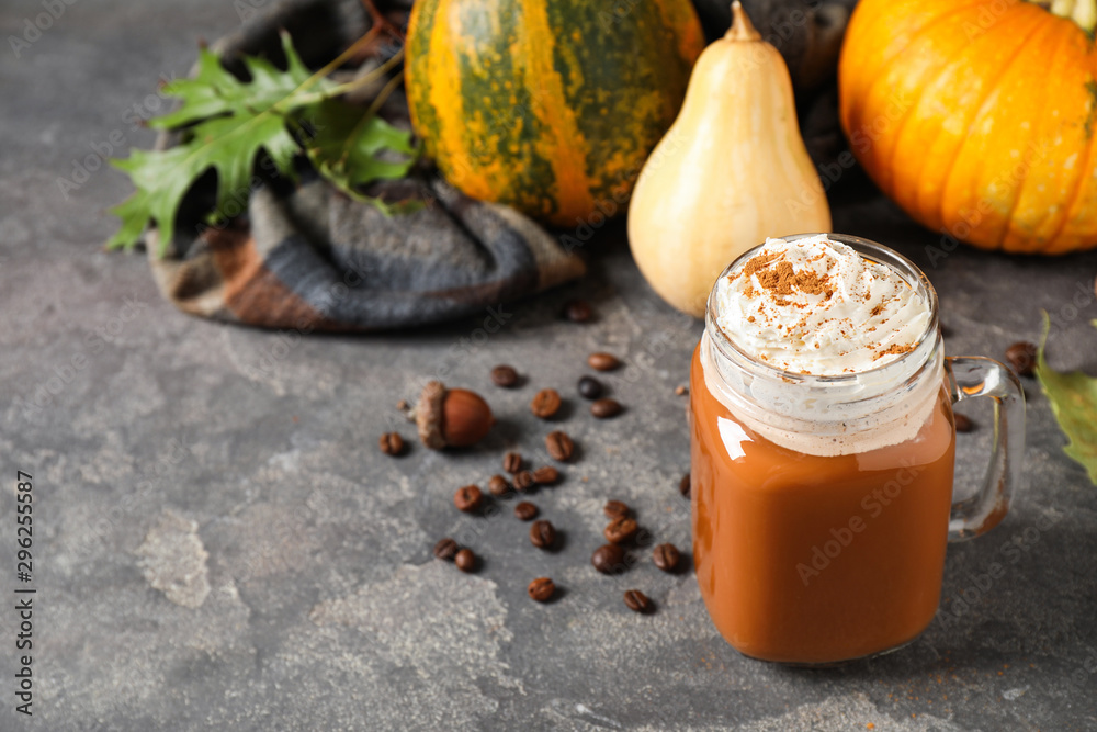 Fototapeta Mason jar with tasty pumpkin spice latte on grey table. Space for text