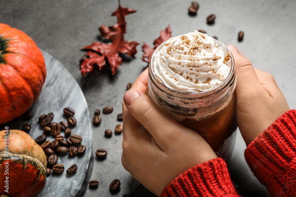 Fototapeta Woman holding mason jar of tasty pumpkin spice latte at grey table, closeup