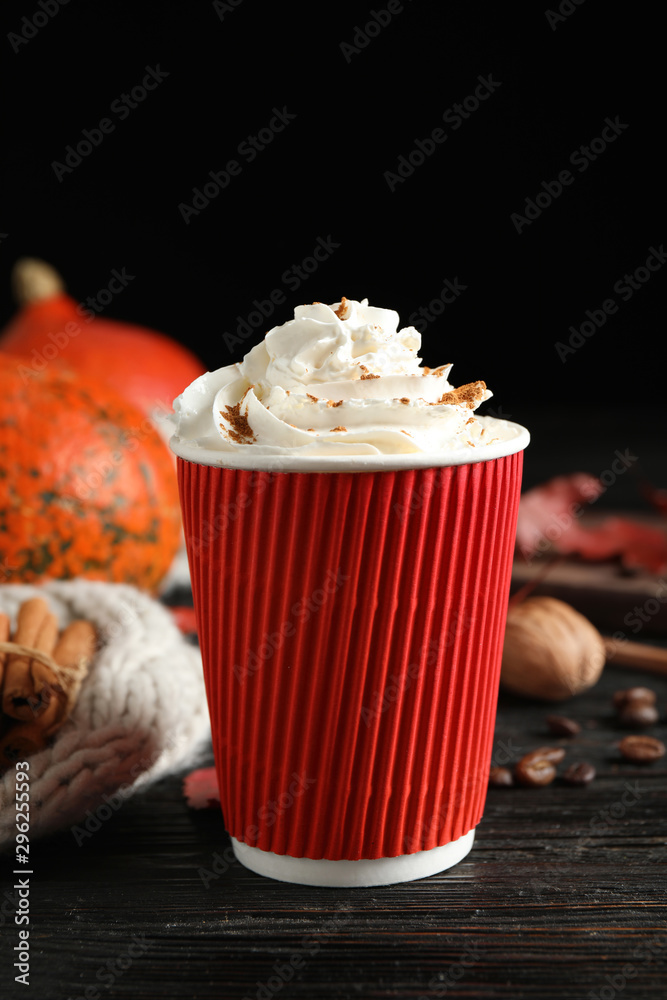 Fototapeta Paper cup with tasty pumpkin spice latte on black wooden table