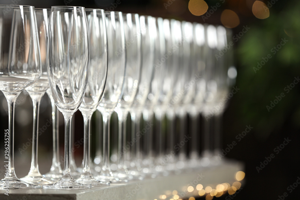 Fototapeta Set of empty glasses on grey table against blurred background