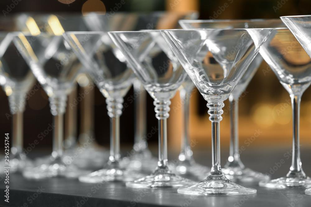 Fototapeta Empty martini glasses on table against blurred background