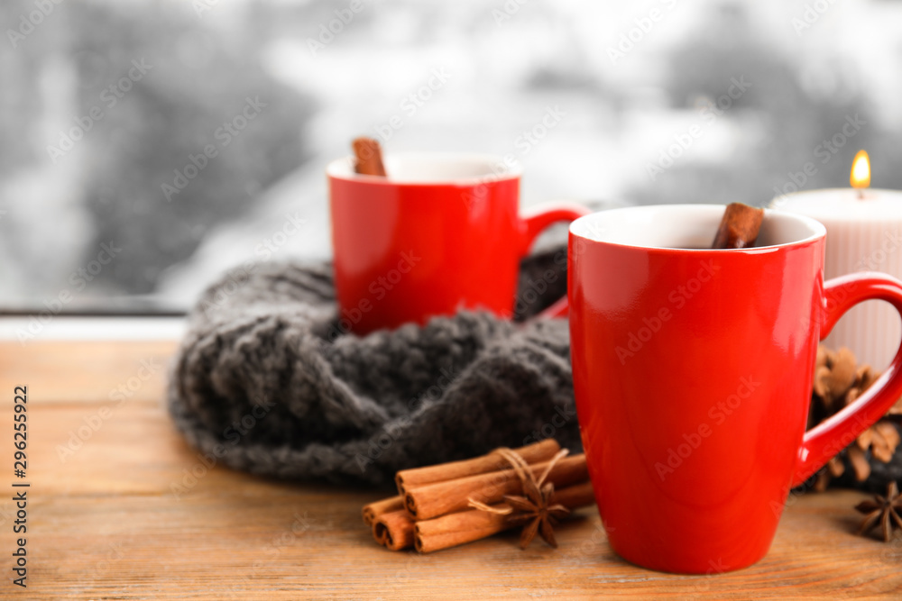 Fototapeta Cups of hot winter drink with scarf on window sill indoors