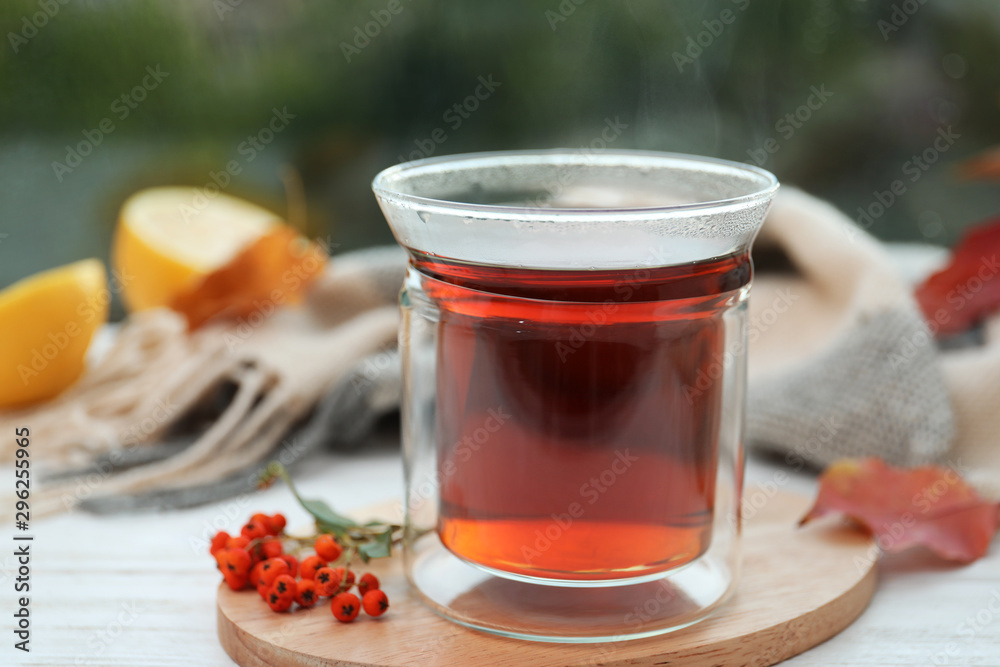Fototapeta Cup of hot drink and scarf on window sill indoors. Cozy autumn atmosphere