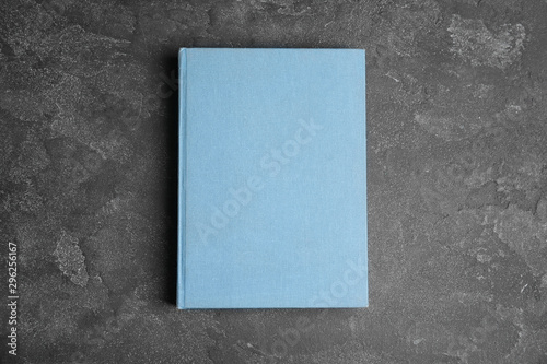 Hardcover book on grey stone table, top view. Space for text Wallpaper Mural