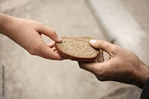 Woman giving poor homeless person pieces of bread outdoors, closeup Wallpaper Mural