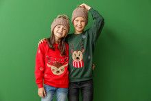 Little Children In Christmas Sweaters And Knitted Hats On Color Background