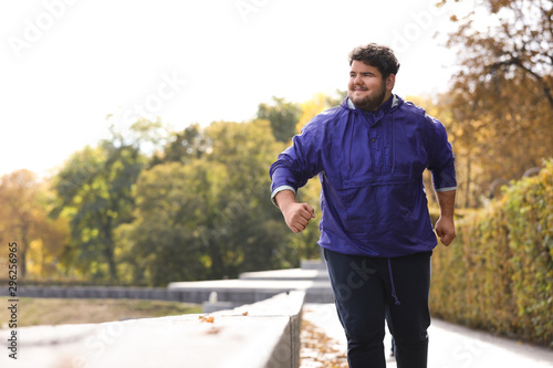 Young overweight man running in park. Fitness lifestyle Fototapete