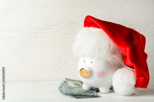 Piggy bank with Santa hat and dollar banknotes on white wooden table. Space for text