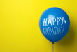 canvas print picture - Blue balloon with words HAPPY BIRTHDAY on yellow background, space for text