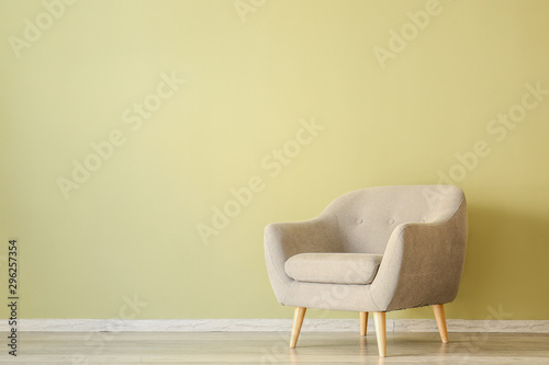 Fotomural  Stylish armchair near color wall in room
