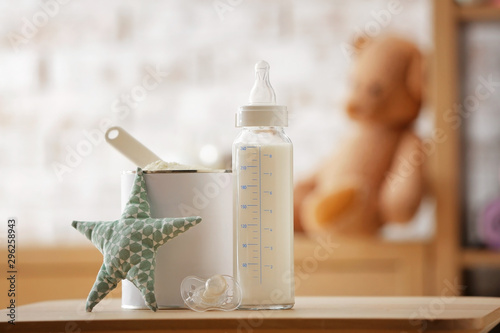 Obraz Bottle of milk and jar with baby formula on table in room - fototapety do salonu