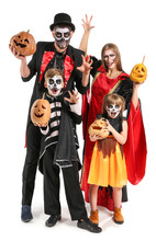 Family In Halloween Costumes And With Pumpkins On White Background
