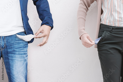 Fotomural  Man and woman showing empty pockets on wall background.