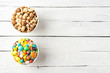 Comparison of healthy and unhealthy snacks. Mixed nuts and sweet in bowls on white wooden background with copyspace