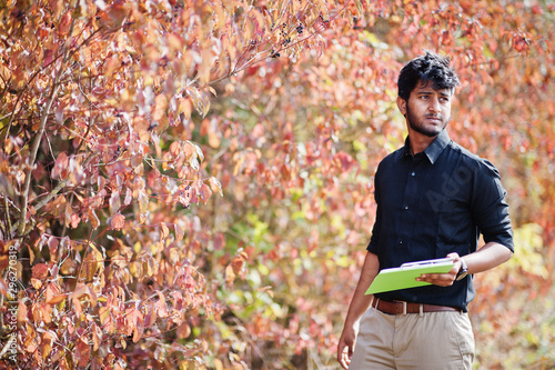Fototapeta South asian agronomist farmer with clipboard inspecting trees in the farm garden. Agriculture production concept. obraz