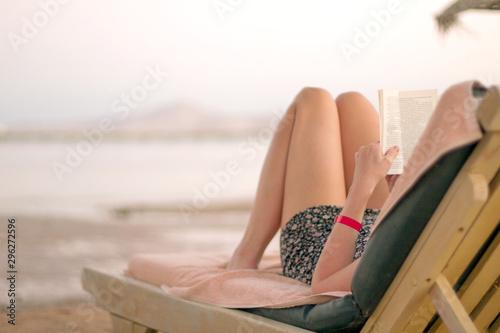 Pinturas sobre lienzo  Woman reading book on the beach
