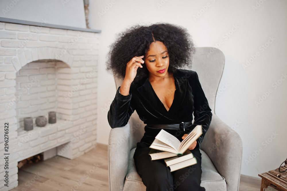 Fototapety, obrazy: Stylish african american woman in black posed at room against fire place read books.