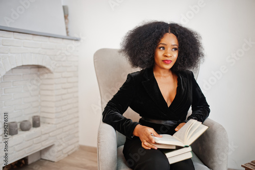 Pinturas sobre lienzo  Stylish african american woman in black posed at room against fire place read books
