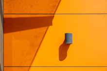 Exterior Industrial Wall Mounted Cylinder Lamp On Modern Orange Wall With Strong Shadows In Bright Daylight And Copy Space