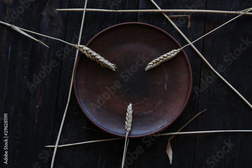 Vászonkép  three wheat spikelets on a clay plate on a black burnt