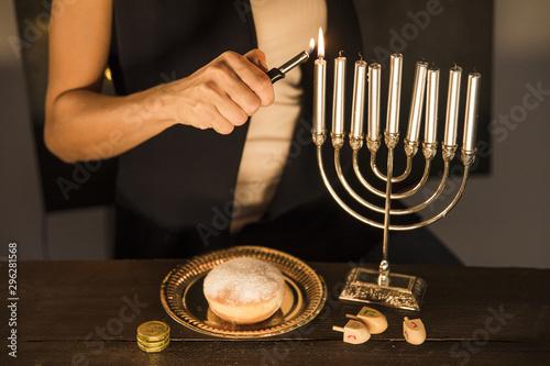 Fotomural  Crop woman lighting candles on menorah