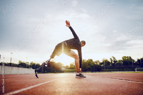 Highly motivated handsome caucasian sporty handicapped man in sportswear and with artificial leg stretching before running while standing on racetrack Fototapeta