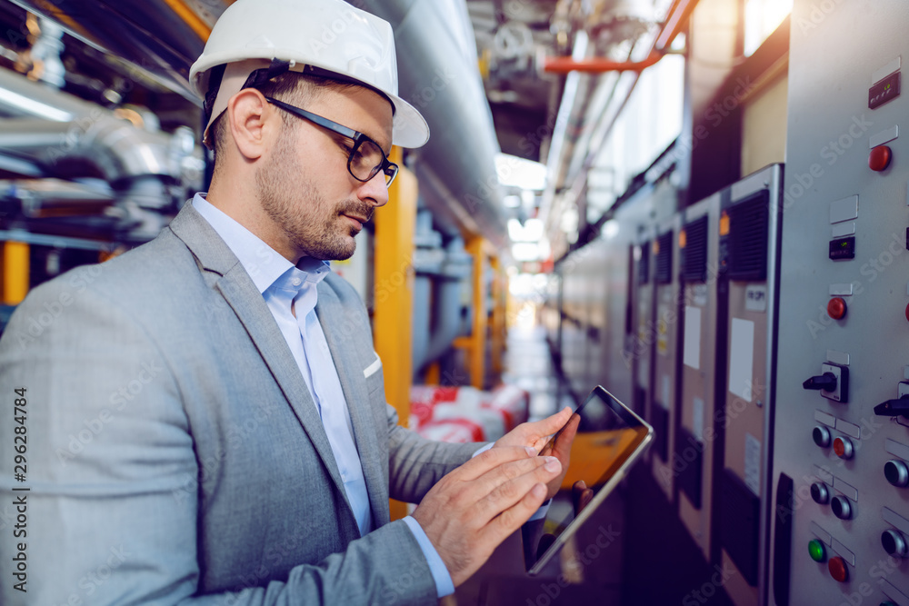 Fototapety, obrazy: Side view of caucasian supervisor in suit and with helmet on head using tablet while standing in front of dashboard in power plant.