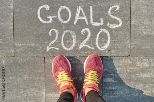 Fototapeta 2020 goals, written on gray sidewalk with woman legs in sneakers, top view obraz