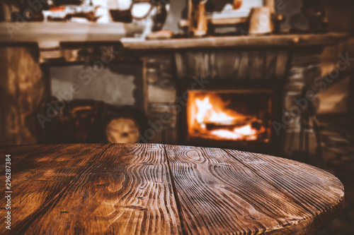 Obraz Table top with blurred fireplace and cosy home interior background. - fototapety do salonu