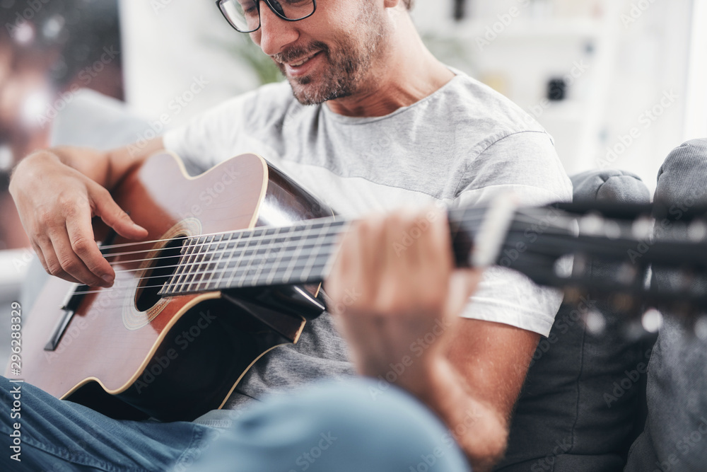 Fototapety, obrazy: Man playing acoustic guitar in the living room.