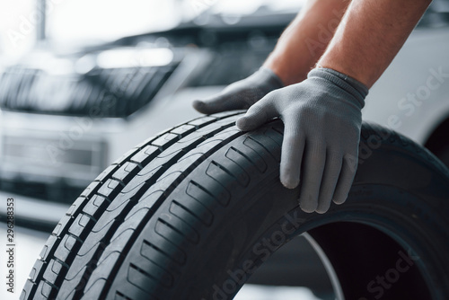 Hands only. Mechanic holding a tire at the repair garage. Replacement of winter and summer tires