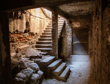 Old Abandoned Tunnel In The Slum Underground Cellar. Entrance To Urban Catacombs. Underside Of City Overpass Concrete Old Worn Repair Dirty Industrial Construction Infrastructure Arch Beam